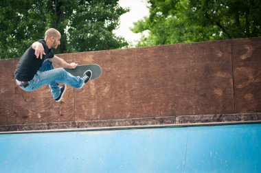 Skateboarder jumping in halfpipe at skatepark.