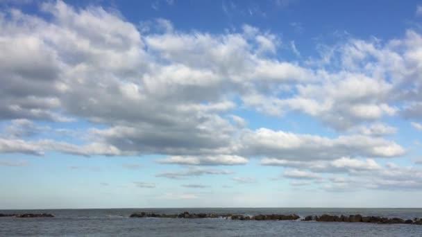 modrá obloha s mraky nad mořem