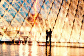 Couple kissing in front of Louvre Pyramid
