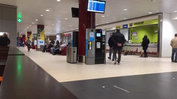Turisté chůzi uvnitř letiště Bologna