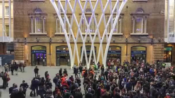 Lidí, kteří jdou uvnitř nádraží Kings Cross železniční