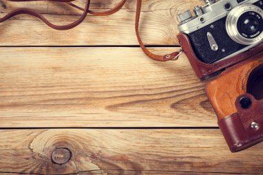 Old retro camera on wooden table background. Copy space. Top view stock vector
