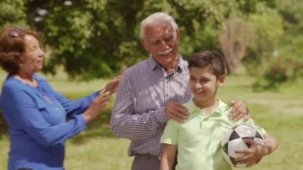 Ritratto felice famiglia nonni e ragazzo con il pallone da calcio
