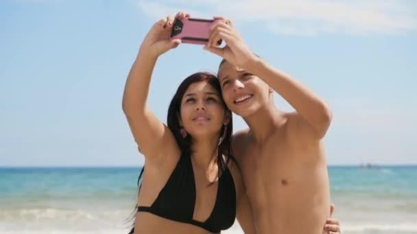1dospívající dívka a chlapec s Selfie s telefonem na pláži