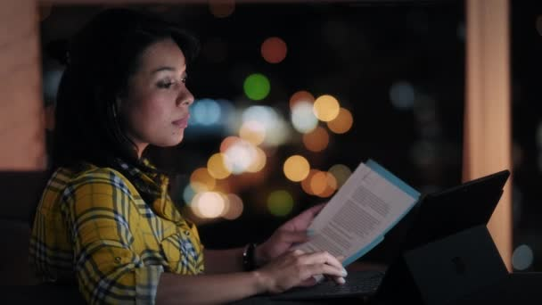 Geschäftsfrau liest Vertrag auf Sofa in der Nacht. Junge Lateinamerikanerin arbeitet spät von zu Hause, überprüft Dokumente und benutzt Laptop-Computer. Menschen und Arbeit