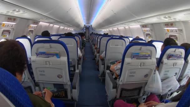 TOKIO / JAPAN - červen 2019: Letadlo létá na obloze s Japonci na palubě. Letadlo asijské letecké společnosti s cestujícími během hrbolatého letu a turbulencí v Japonsku v Asii. Vnitřní pohled na kabinu