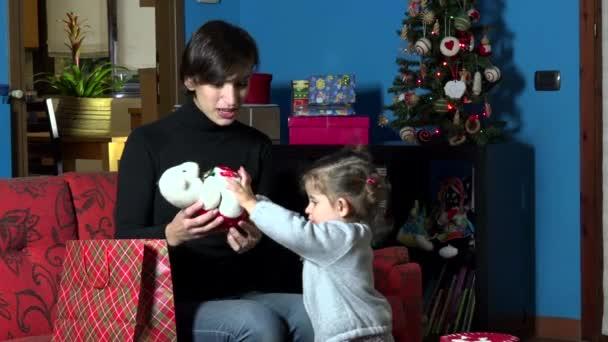 Matka a dítě otevře vánoční dárek přítomen během zimních prázdnin
