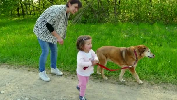 Maminka a dcera usmívající se pes domácí zábava v parku