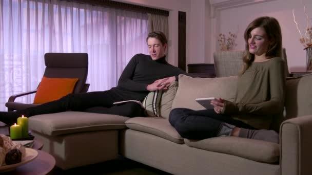 Mladý muž a žena odpočívat doma s noviny Ipad
