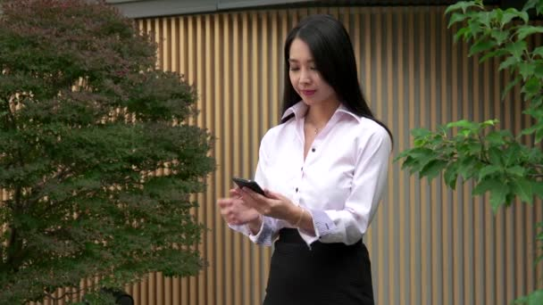Beautiful Asian Woman Talking On Mobile Phone Near Office Building