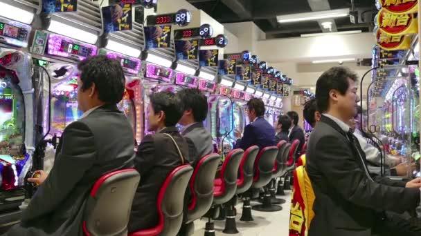 Japonští muži lidí hraje Pachinko hra kasinových Tokio