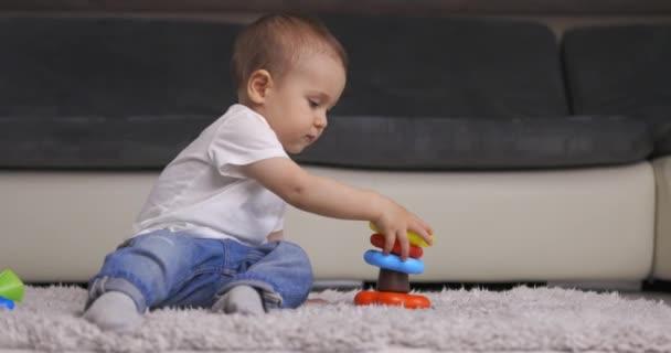 Roztomilý chlapeček hrající si s barevnou pyramidovou hračkou doma