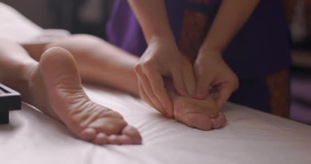 A fiatal és gyönyörű nő lábmasszázst kap a spa szalonban. Egészséges életmód és testápolás koncepció. Közelkép, lassított felvétel.