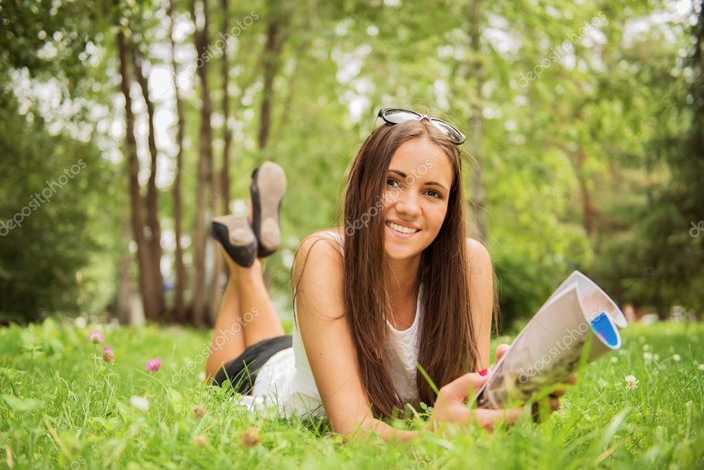 A young brunette woman lying on the grass outdoors with her foot