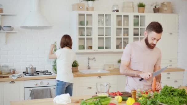 Young couple cooking together in kitchen preparing dinner chopping carrot at home