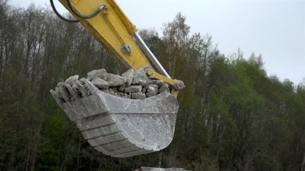 The backhoe with lots of rocks on it