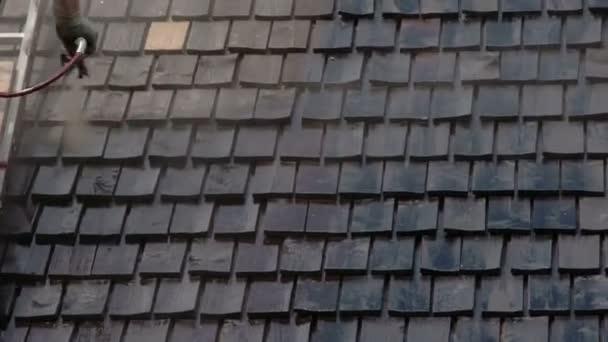 Čištění dřevěných šindelů ze střechy domu.