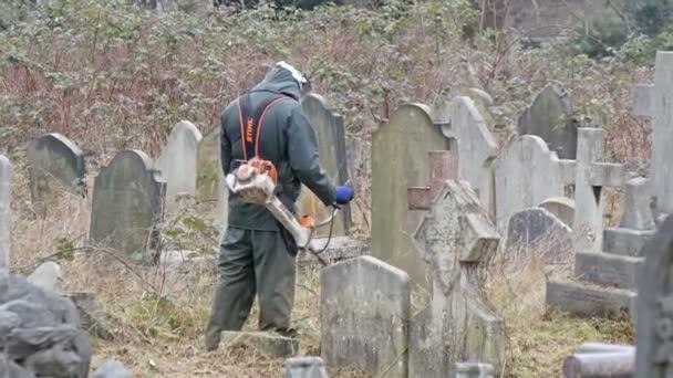Muž, sekání trávy na hřbitově