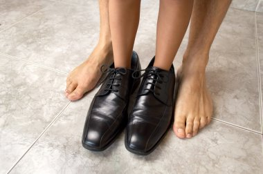 child with father shoes and his barefoot father