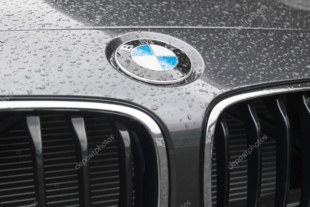 BMW logo on wet surface of car hood