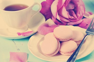 Stylish elegant afternoon tea with macarons and roses.