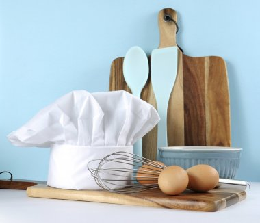 Modern blue and white kitchen with chefs hat and utensils.