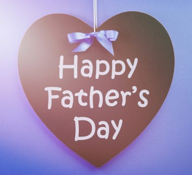 Happy Fathers Day message written on a black blackboard with blu