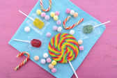Assorted candy and lollipop on pink wood table.