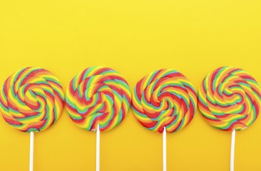 Rainbow lollipop candy on bright yellow wood table.