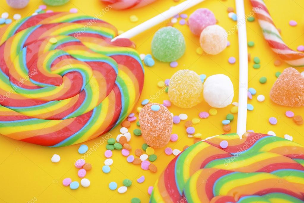 Rainbow lollipop candy on bright yellow wood table  — Stock Photo