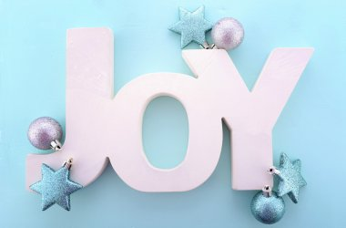 Festive Christmas greeting, with the word, Joy, spelled in wooden letters with ornaments on a pale blue background. stock vector