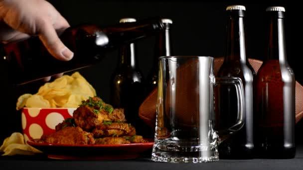 Mužské ruky nalil pivo do stein skla s amerického fotbalu, občerstvením a lahví piva.