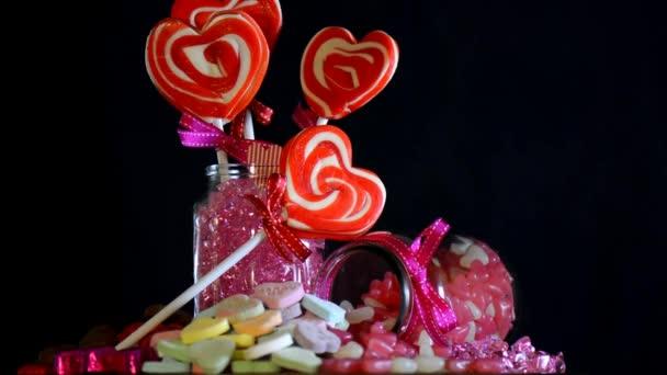 Mans ruka držící se srdce ve tvaru lízátka z hromady cukroví, Valentýn