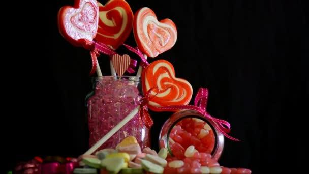 Valentinky den cukroví včetně srdce tvaru lízátka a různé sladkosti do pomalé rotace na černém pozadí
