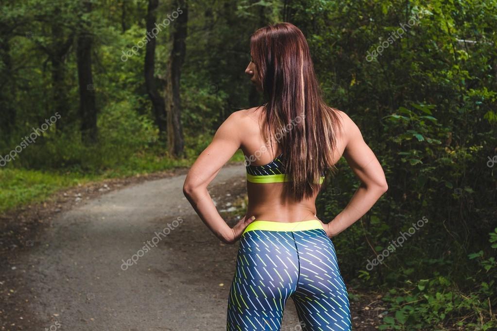 Imagen de mujer joven atlética frotando los músculos de su espalda ...