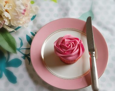 Overhead of pink rose frosted cupcake on vintage plate