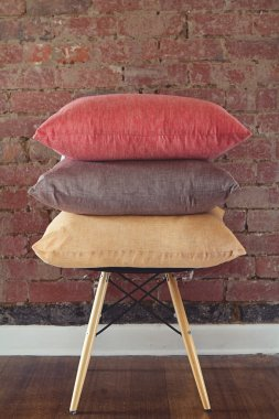 Stack of three linen cushions on chair