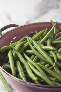 Close up of a pink colander with washed green beans