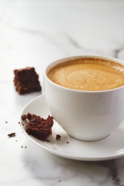 Crumbling chocolate brownie on latte coffee cup and saucer