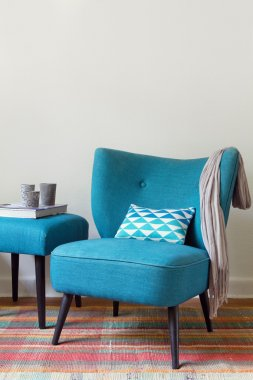 Teal retro armchair and ottoman with decor objects
