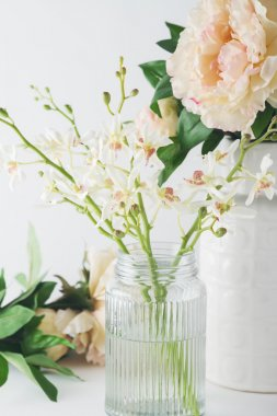 Close up of white orchid flowers in a glass vase with roses in b