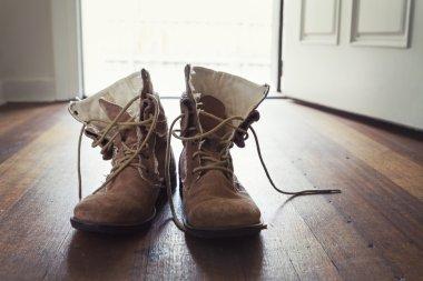 Pair of men's worn leather boots in doorway of home
