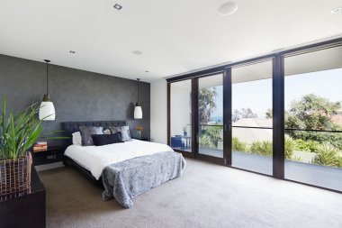 Spacious interior of designer master bedroom in luxury Australia