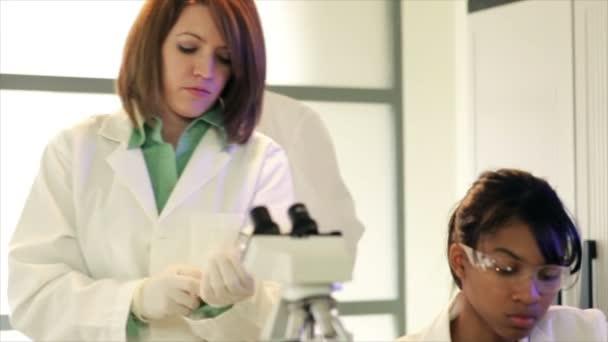 Laboratorní technik dívá do mikroskopu