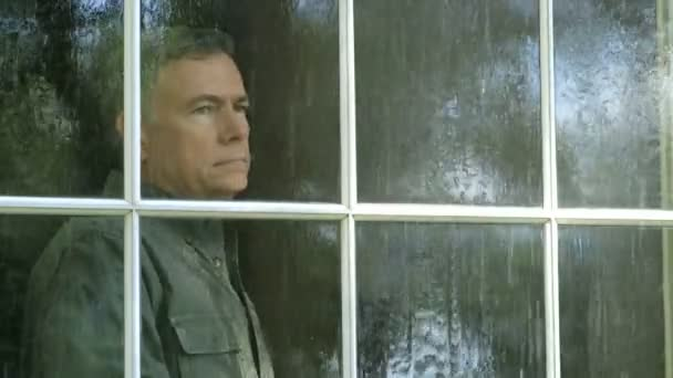 outside view of a man looking out a window during a rain storm