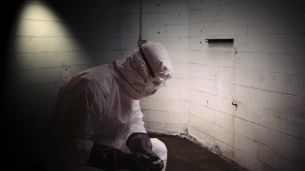 Médico de HAZMAT tomar muestra de sangre en el cuarto oscuro