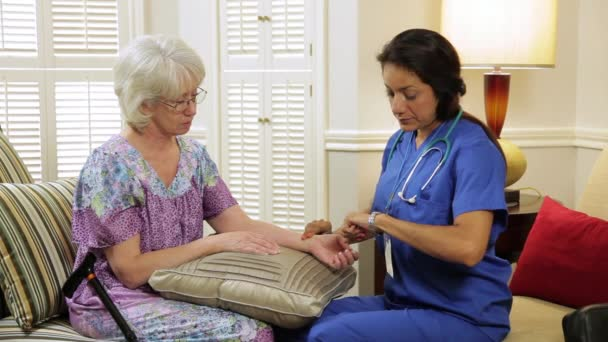 home healthcare nurse taking pulse of her patient