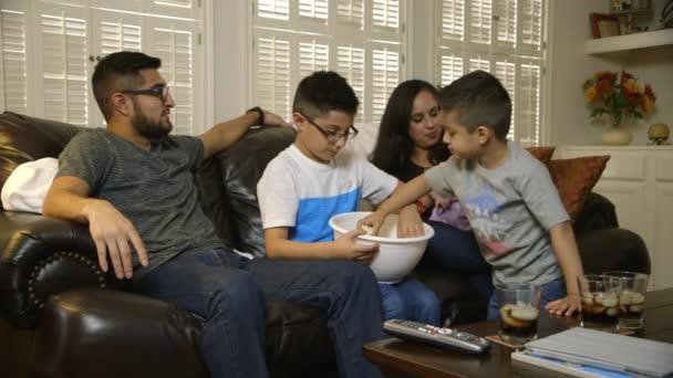 mladá hispánský rodina jíst popcorn a sledování televize