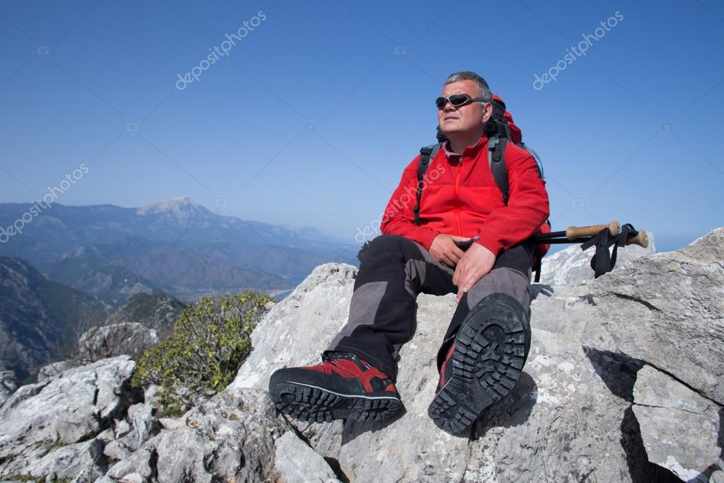 A traveler stands on top of a mountain and looks out to sea.