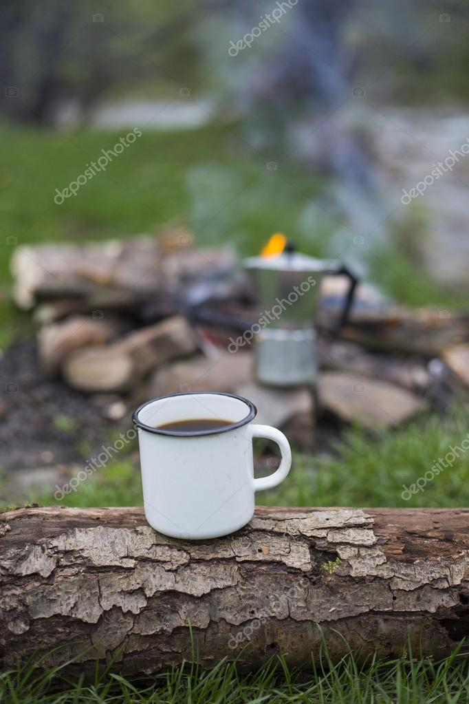 The cup stands on a log on the fire background.